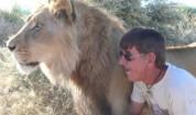 Мъж прегръща и целува лъв