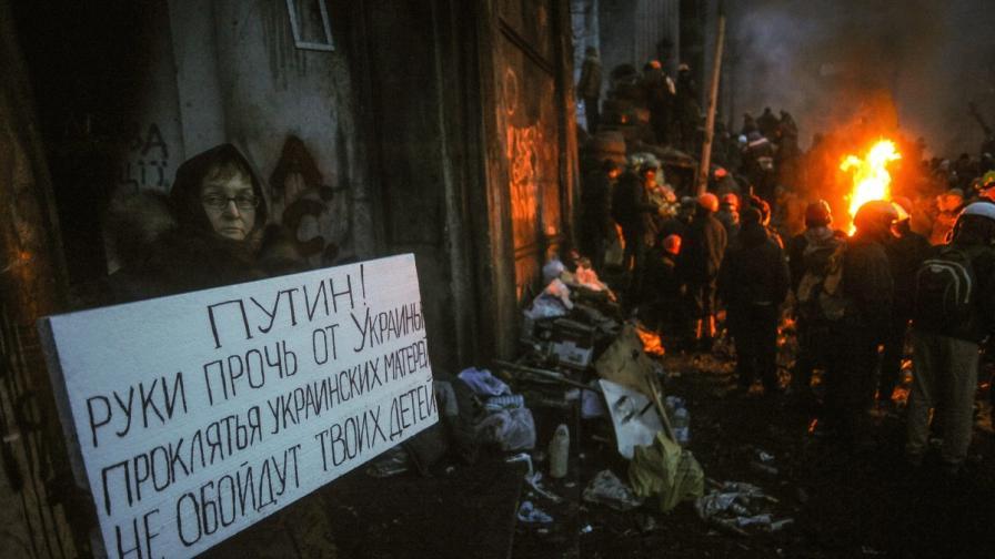 """Жена държи плакат с надпис """"Путин, долу ръцете от Украйна"""" на протест в Киев"""