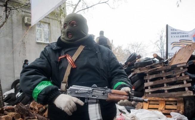 Въоръжен с автомат мъж пред барикада, издигната от проруски протестиращи в Славянск