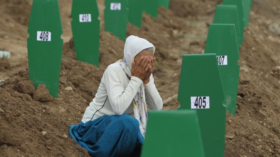 Жена плаче над гробове на жертви от клането в Сребреница