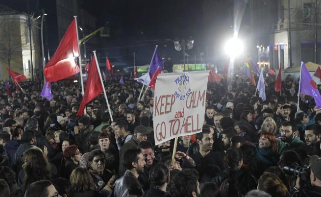 Спокойно и отивайте по дяволите - това пише на плакат, издигнат от поддръжниците на СИРИЗА. Нецензурният жест е отправен към тройката  МВФ, ЕЦБ и ЕС