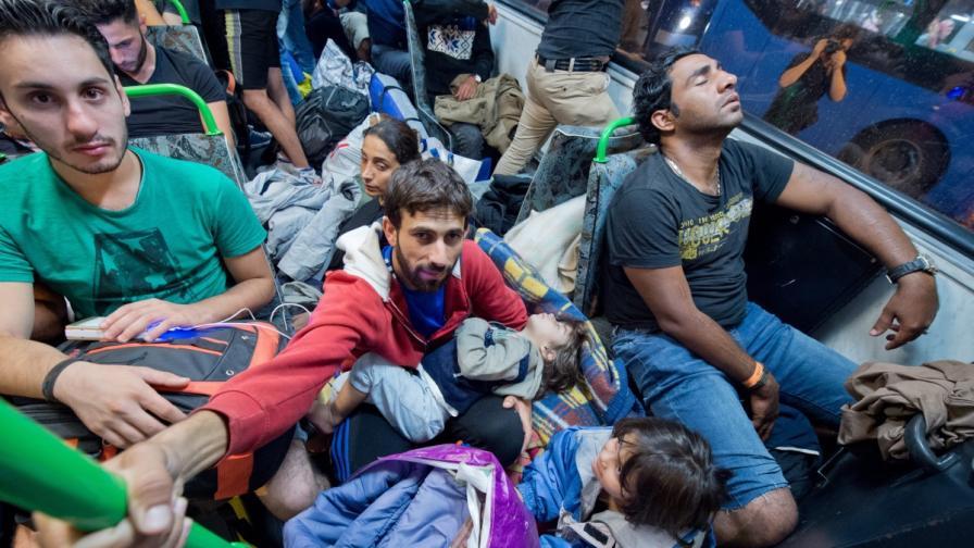 Бежанци пътуват в един от автобусите от Унгария към границата с Австрия