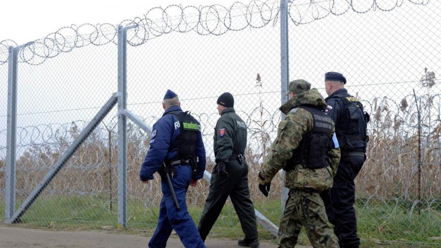 Унгарски и словашки полицаи заедно с полски граничар и чешки полицай патрулират край временната ограда на границата между Унгария и Сърбия