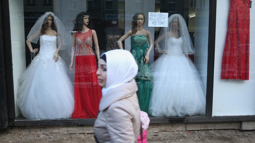 Мюсюлманка минава покрай магазин за булчински рокли в Германия