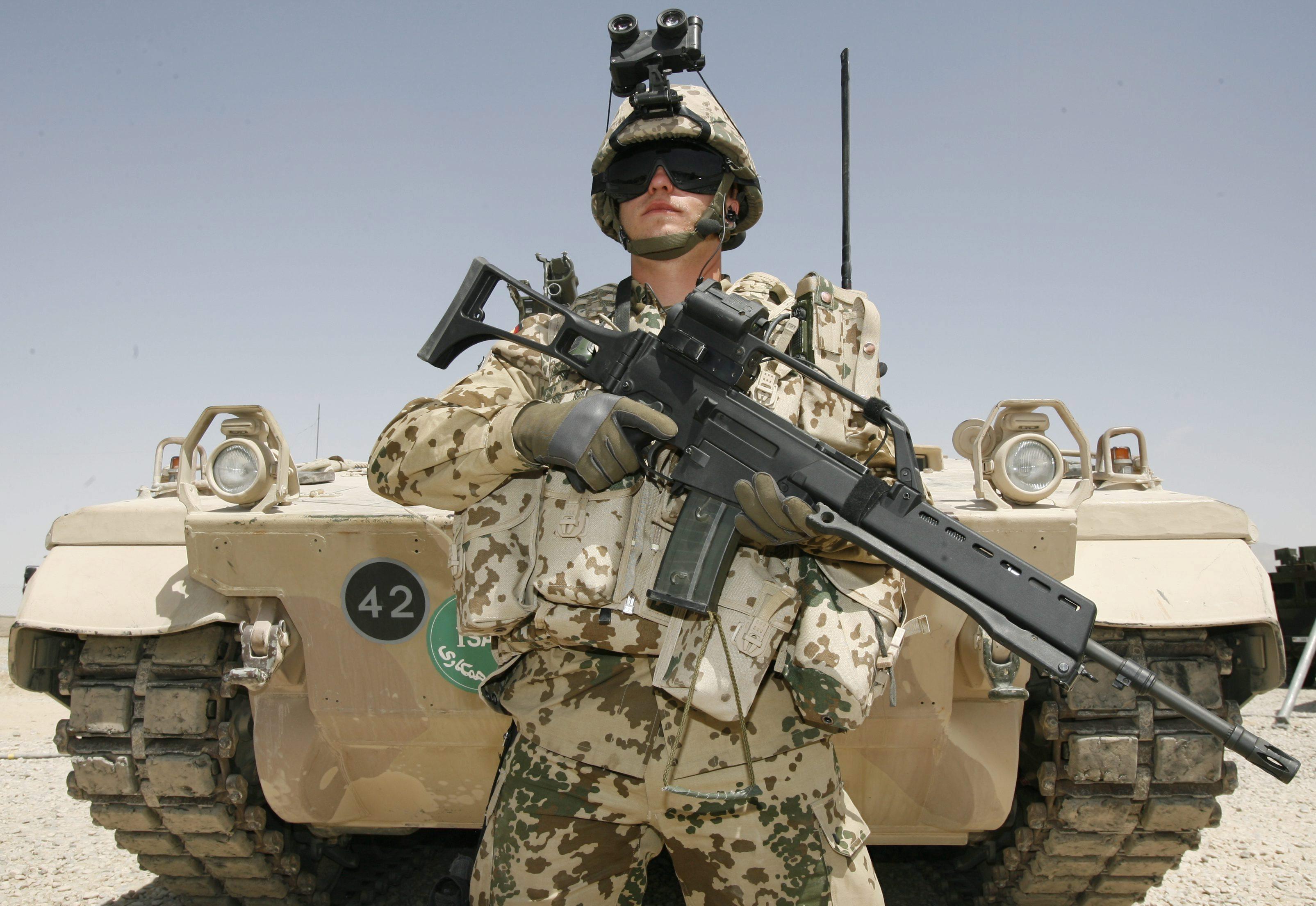 Германски войник, въоръжен с автомат Heckler & Koch G36, стои пред бронирана машина Marder1 A5M в Афганистан