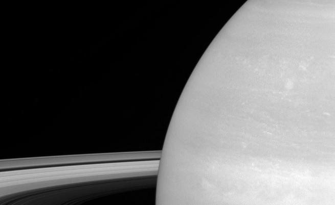 Луната Мимас на фона на Сатурн. Луната е с диаметър 396 км.