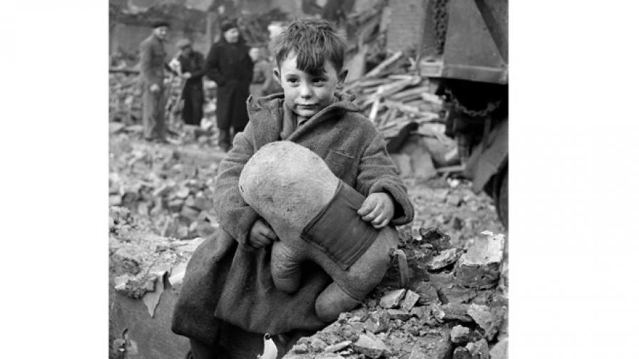 С играчка в ръка, сираче стои на прага на разрушения си дом