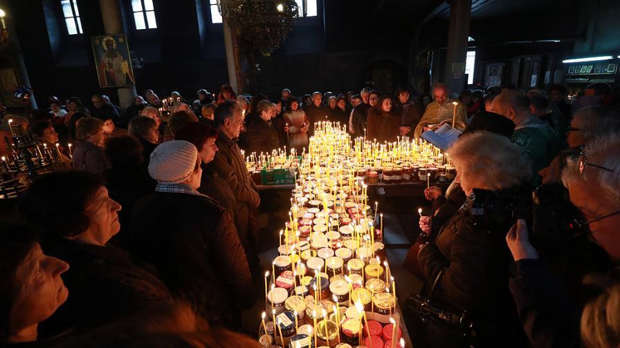 """Ритуалът за освещаване на мед в катедралния храм """"Въведение Богородично"""" в Благоевград. Бурканчетата, донесени за освещаване са подредени според утвърдилия се през годините обичай върху маси под формата на кръст със свещи върху всяко от тях. Свещите се запалват след празничната Света литургия и в центъра на храма засиява огромен огнен кръст."""