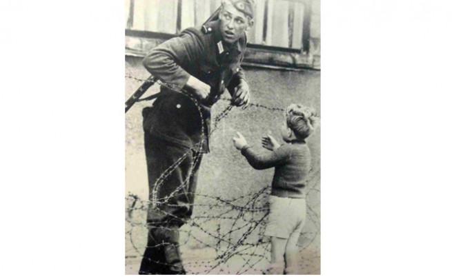 Войникът от Източен Берлин помага на малкото момченце.