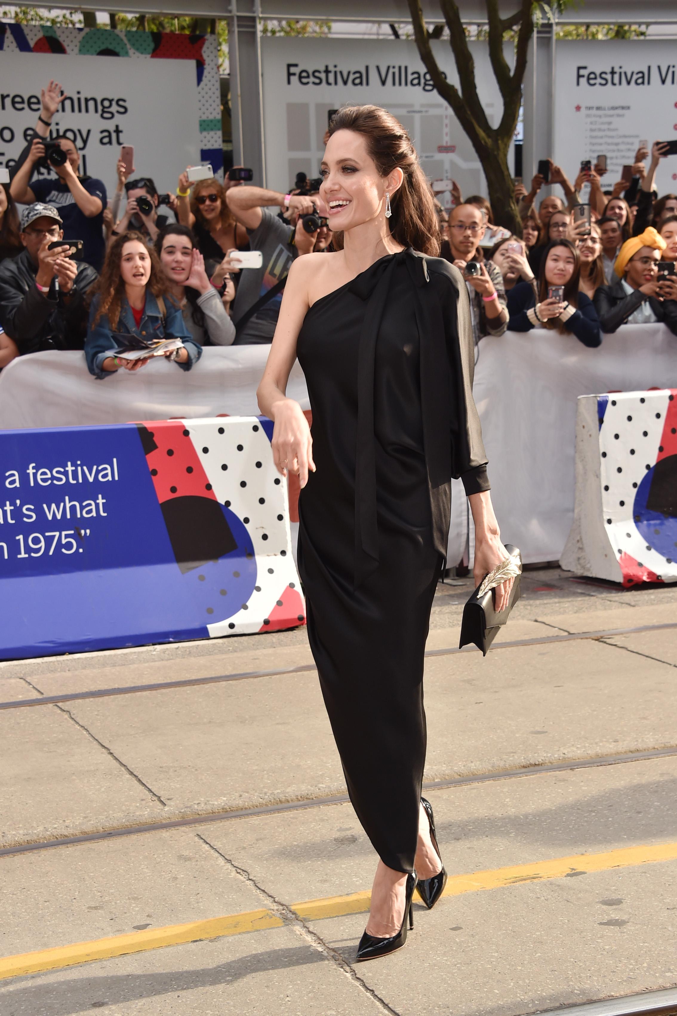 """42-годишната актриса завладя червения килим по време на канадската премиера на филма """"Първо убиха баща ми"""", който самата Анджелина продуцира.Красивата звезда бе облечена в семпла, но елегантна черна рокля от коприна, съчетана с черни обувки на висок ток.На събитието Джоли не бе сама - придружаваха я нейните 6 деца, включително от 16-годишният Мадокс, който е осиновен от Камбоджа, където се развива и действието в """"Първо убиха баща ми""""."""