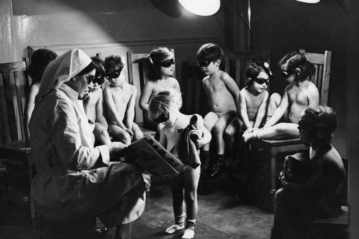 """На снимката, заснета на 2 март 1942 г. в Лондон се вижда медицинска сестра, която стои с група деца в стая за тен. По време на войните и особено в зимните месеци ограничените хранителни продукти и липсата на слънчева светлина се отразяват най-много върху човешкия организъм. Точно затова на места децата изкуствено са облъчвани със """"слънчеви лъчи""""."""