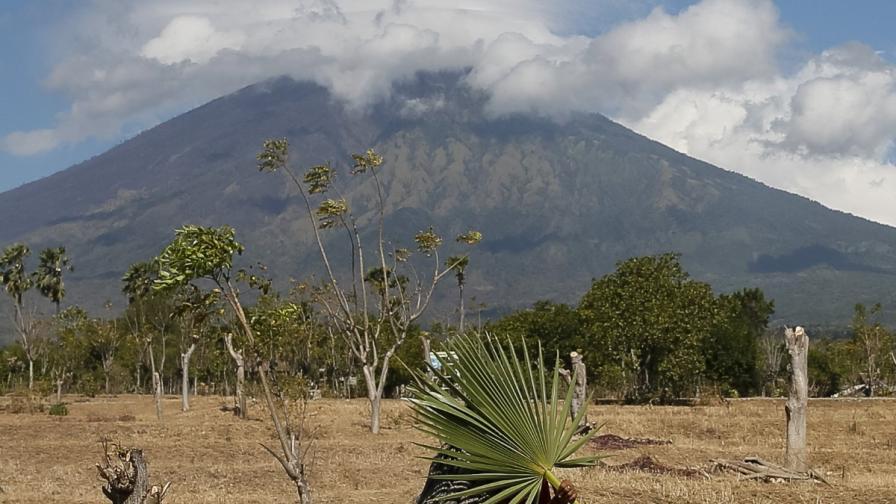 Жена върви на фона на вулкана Агунг на о-в Бали