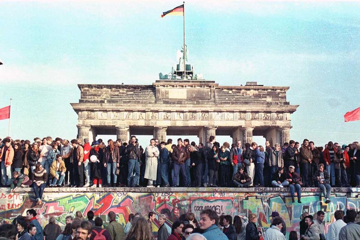 Граждани на Западен Берлин празнуват върху Берлинската стена пред Брандербургската врата на 10 ноември 1989 г.,след като на 9 ноември 1989 г. правителството на Източна Германия отменя ограниченията за излизане от Германската демократична република.