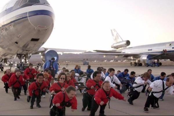Група от малки хора теглят самолет... причината е неизвестна, резултатът се подразбира.