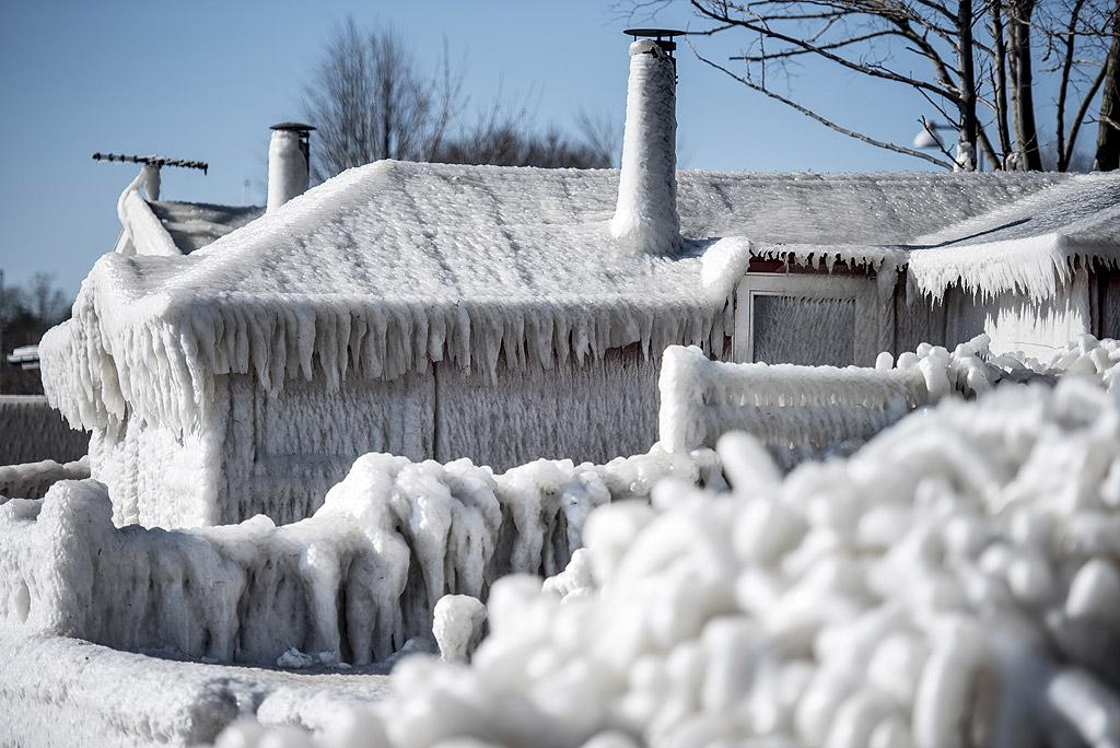 Къща е обгърната от лед на брега в залива Факсе, южно от Копенхаген, Дания,