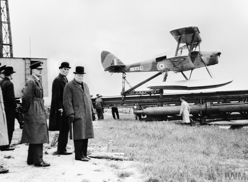 """Британският премиер Уинстън Чърчил наблюдава подготовката по пускането на """"De Havilland Queen Bee"""" L5984. Безпилотният дрон """"Queen bee"""" бе контролиран чрез радио предавател. Събитието се случва на неопоменато място в Обединеното кралство на 6 юни, 1941 г.<br /> <br /> Автор: Хортън У. Г., военен фотограф"""