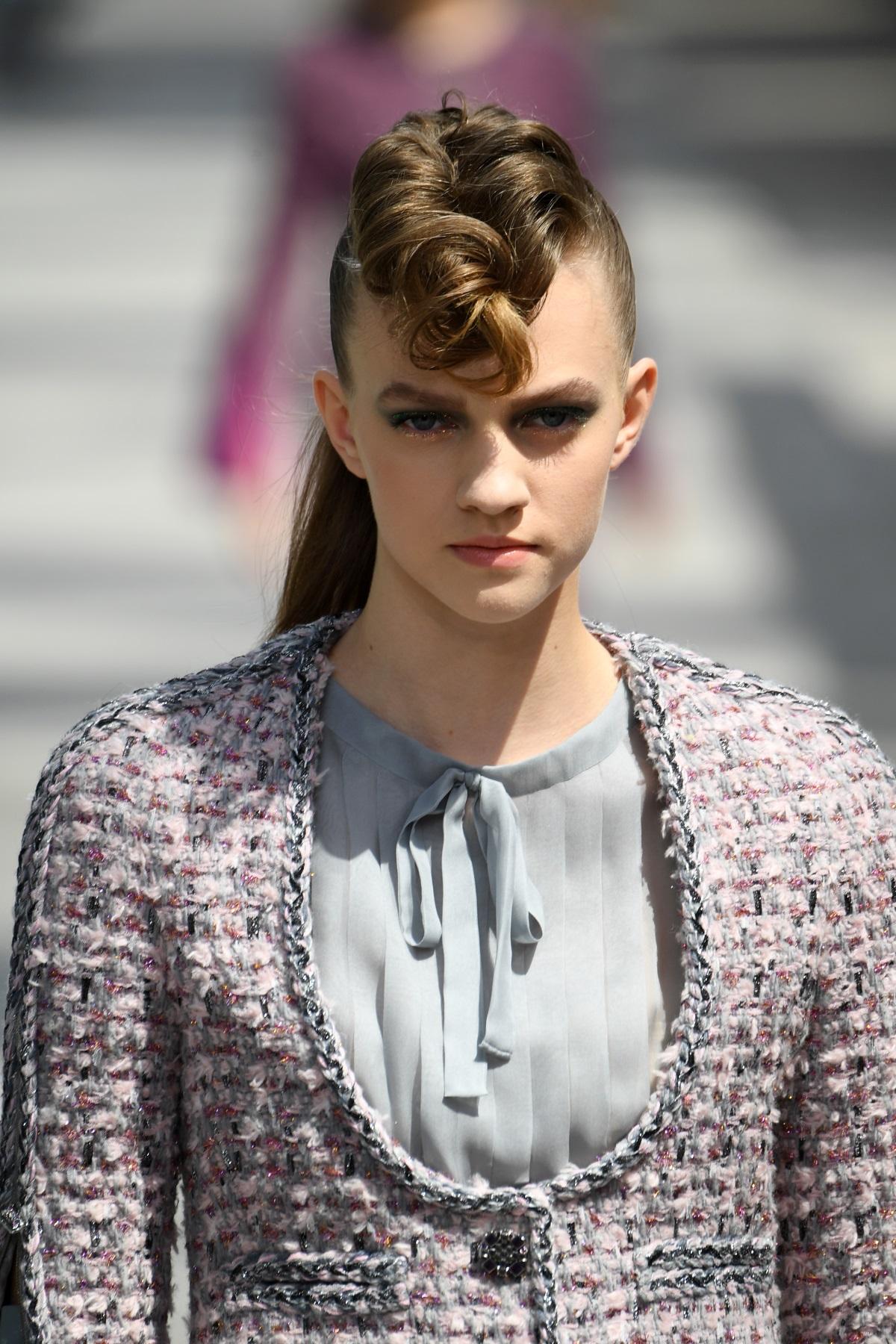 """""""Шанел"""" заложи на прибрани коси, вдигнати на опашка, но не липсваше интересен завършек на прическата. Стилът на моделите е вдъхновен от рокендрол и пънк вълната."""