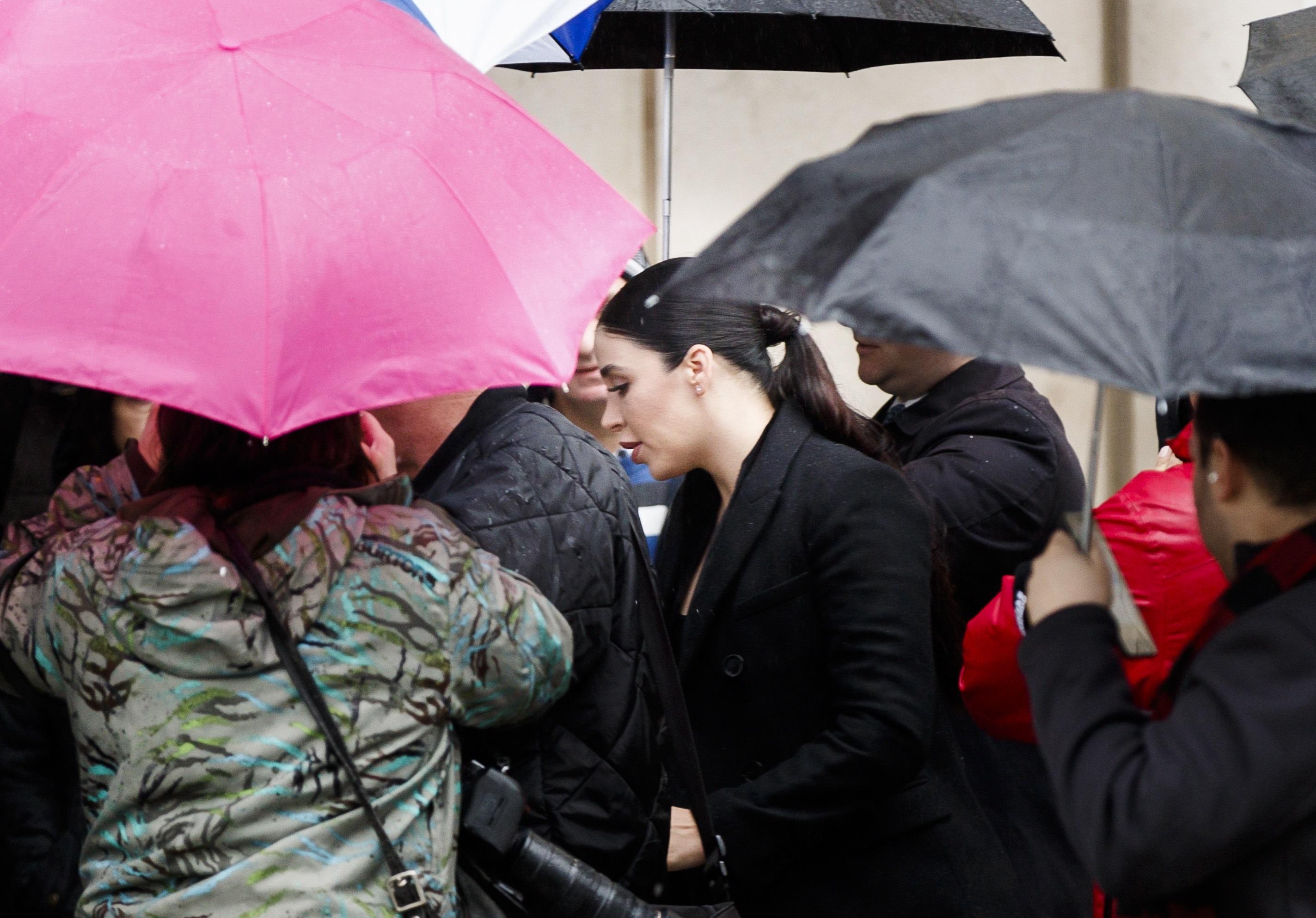 """29-годишната Ема Коронел, бивша кралица на красотата, пристигна в съда в Бруклин, където започна процеса срещу сочения за особено жесток и за най-големия наркодилър в света Хоакин """"Ел Чапо"""" Гусман.  Ема Коронел Айспоро, родена в Америка, се омъжва за мексиканския наркобарон през 2007 г.  Родена на 3 юли 1989 г. в Калифорния, САЩ,смята се, че чичо й е бил убит от доверен на Ел Чапо. Той казва, че се е влюбил в Ема Корнел, когато я е видял в конкурса за красота през 2007 г. Тогава тя е била на 17 години. Той използвал влиянието си, за да спечели. Година по-късно се женят."""