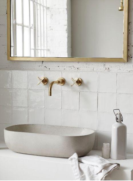 1. Златните елементи превръщат бялата баня в луксозно убежище.