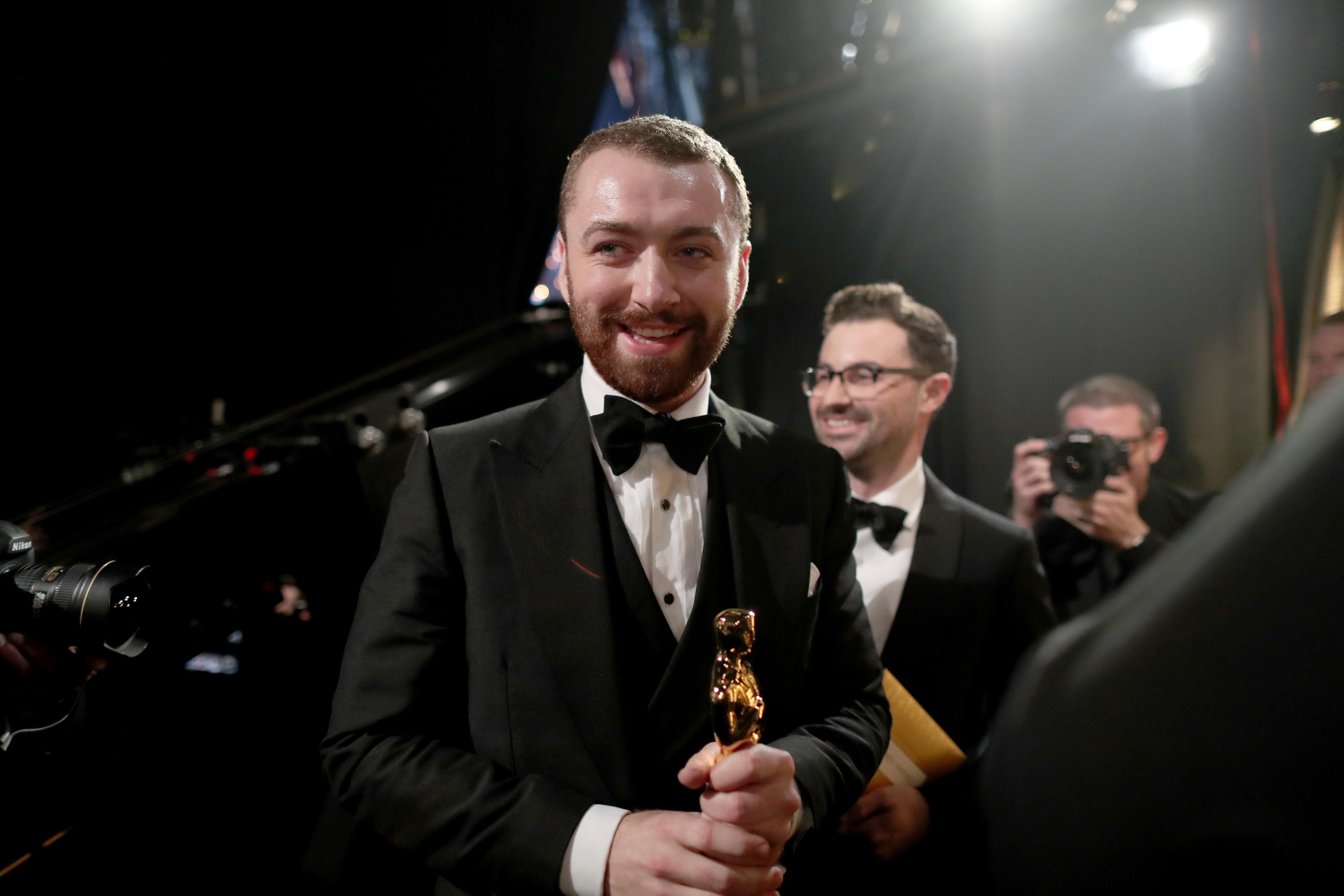 """Сам Смит печели през 2016 г за песентаWriting's on the Wall за филма """"Спектър"""" от поредицата за Джеймс Бонд."""