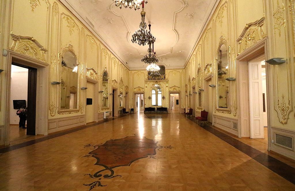 В центъра на тази изложба e Дворецът – една от най-старите сгради в самото сърце на София, тясно свързана с историята на града и на България. Дворецът се представя със своя характер, какъвто е бил на границата между ХІХ и ХХ век, той се разбира и като физическо пространство, създадено както от архитекти и художници, така и от хората, които са го обитавали. Дворецът е топос, мястото на властта и културата, метафоричен образ за фигурата на държавния глава, на княз Александър I Батенберг и на цар Фердинанд. Експозицията заема пространствата, в които е протичал официалният им живот. Тя е обвързана с историята на новото българското изкуство от края на ХІХ – началото на ХХ век.