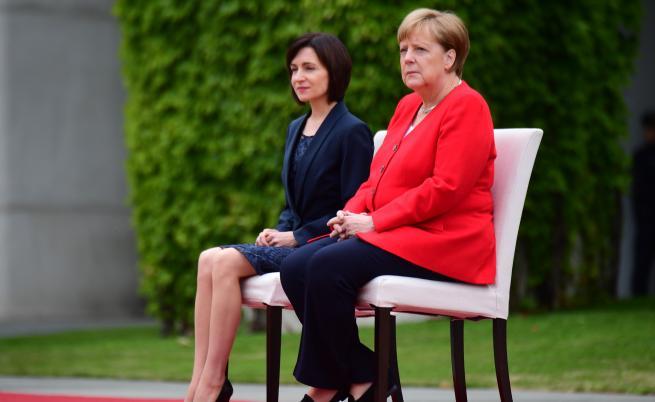 Германският канцлер Ангела Меркел остана седнала при изпълнението на национални химни на официална церемония, заедно с молдовския премиер Мая Санду.