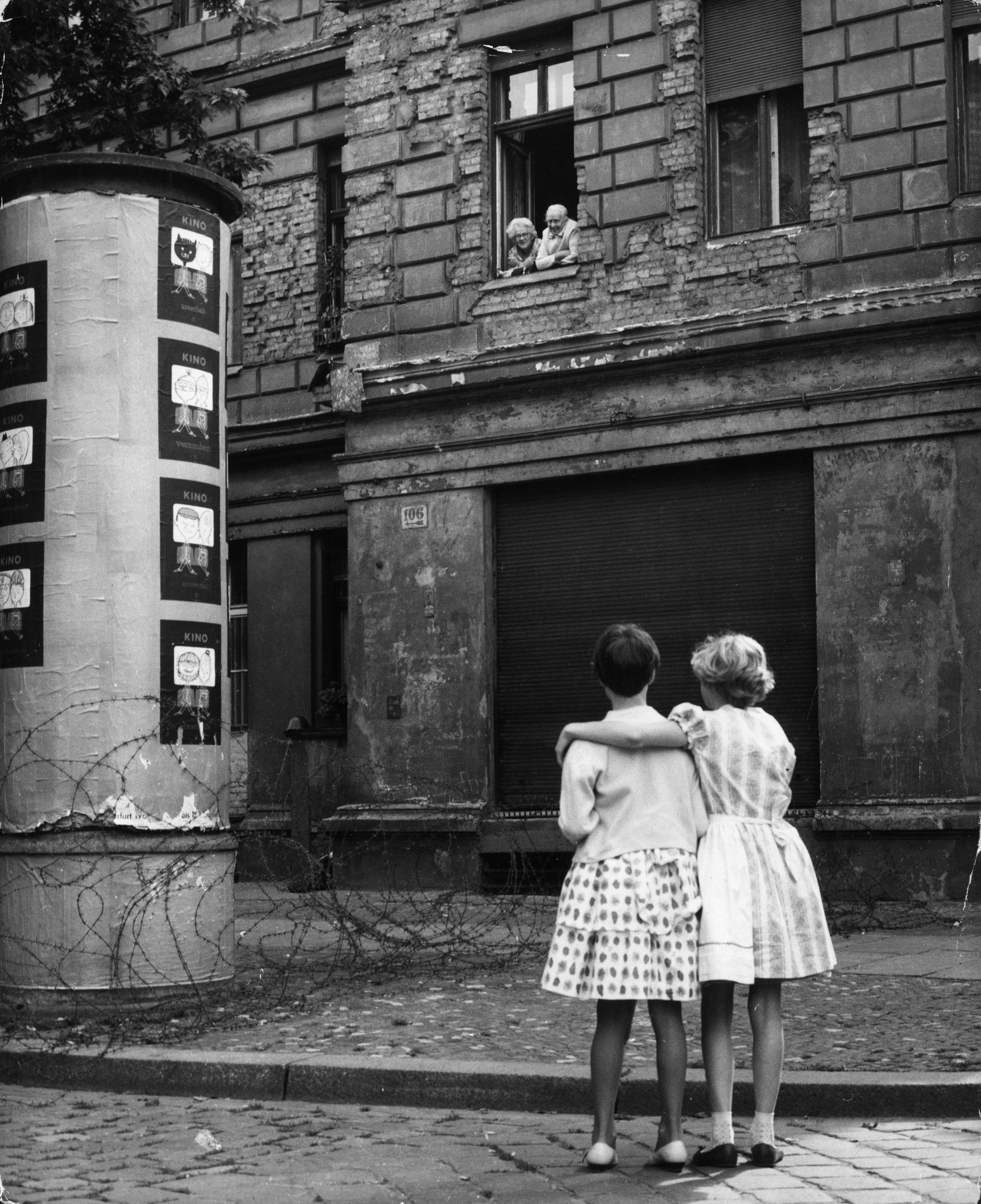 <p><strong>14 август 1961 г.</strong></p>  <p>Две момиченца стоят на западногерманска улица и разговарят с бабата и дядото си, които са застанали на прозореца на дома им, който се намира в източната част. Семейството е разделено от бодливата тел.</p>  <p>&nbsp;</p>