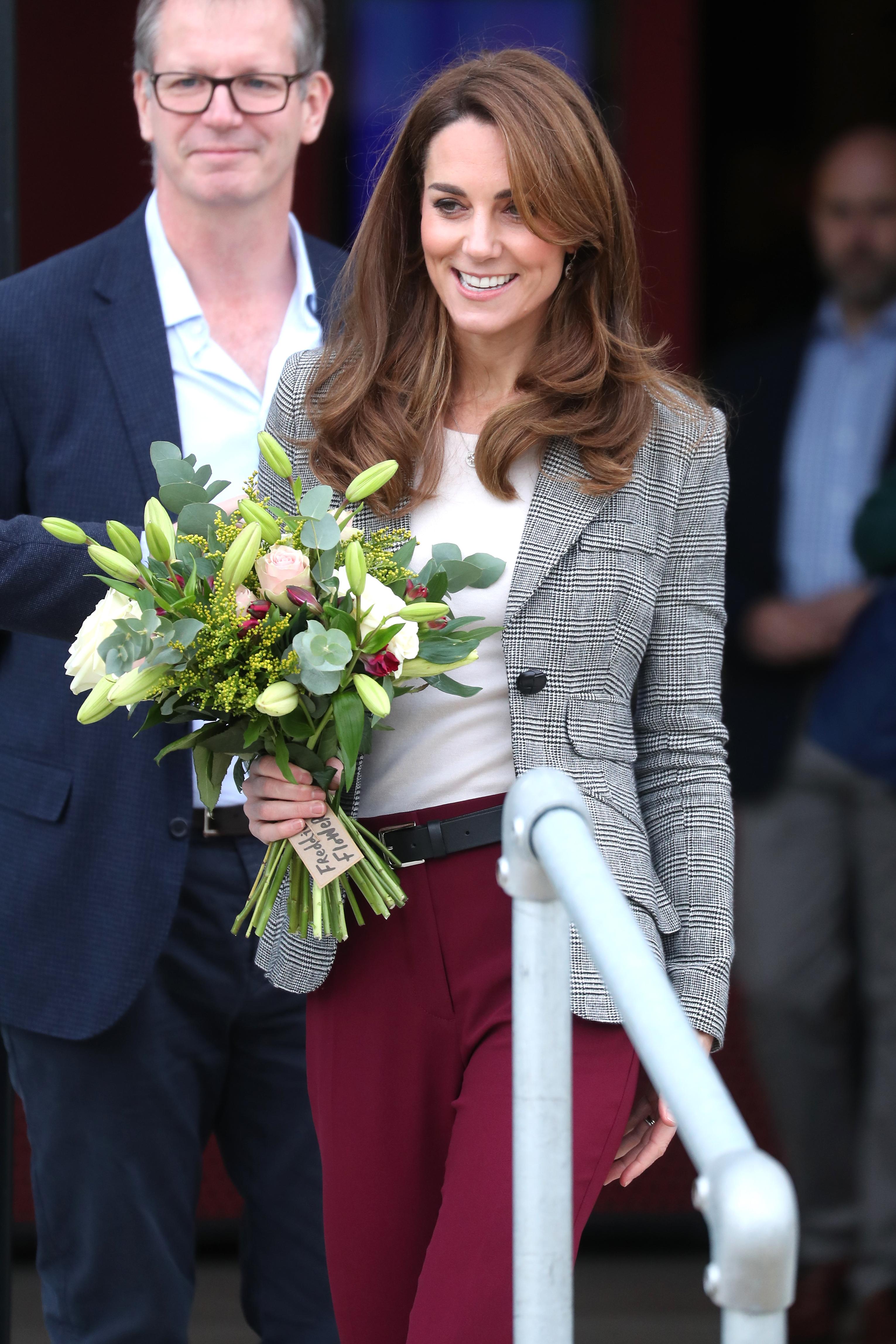 <p>Кейт и принц Уилям присъстваха във вторник на събитие към благотворителна организация, на която са патрон. Вместо с рокля, както по-често виждаме Кейт, херцогинята&nbsp;пристигна с панталон в цвят бургунди, който съчета с бяла блуза и сив блейзър. Кейт бе заложила на черни обувки с дебел ток, които допълни с черен колан</p>