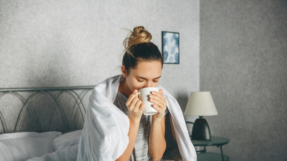 болна жена пие от чаша в леглото у дома