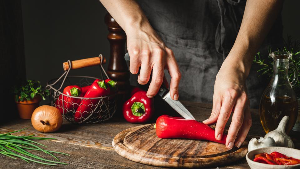 жена готви червени чушки и чесън