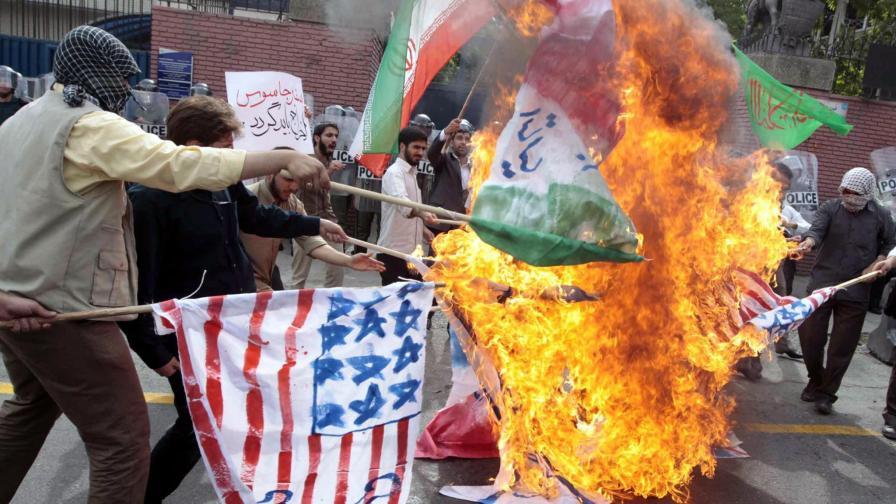 Подръжници на Ахмадинеджад горят британско, американско и израелско знаме пред посолството на Великобритания в Техеран.