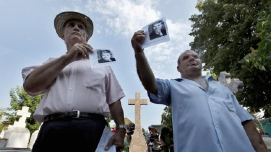 Възрастни румънци демонстрират със снимки на Чаушеску пред гроба на бившия комунистически лидер