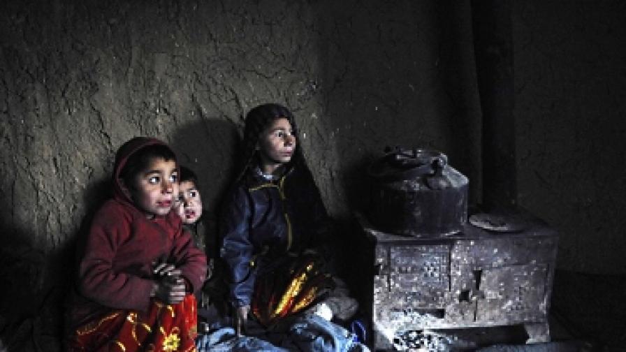 Деца се греят край печка в бежански лагер в Кабул, Афганистан