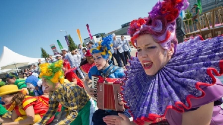Весели артисти, повечето доброволци, посрещат спортистите от цял свят, пристигащи в Олимпийското село
