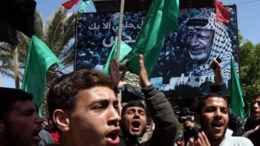 Палестинци носят плакат с портрета на Ясер Арафат по време на протест